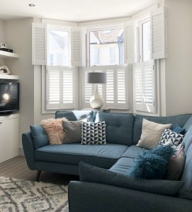 Living room with bay window and white plantation shutters